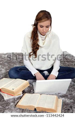 portrait of female student working on bed - stock photo