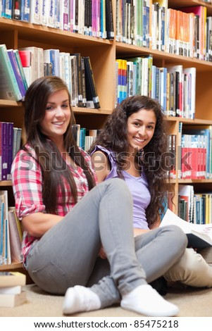 Portrait of female students holding a book - stock photo