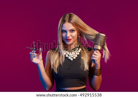 Portrait of female stylist standing with hairdresser's accessories