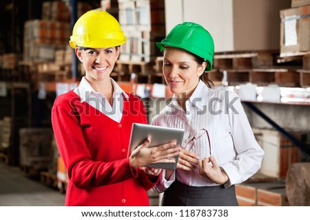 Portrait of female supervisor with colleague working together in warehouse - stock photo