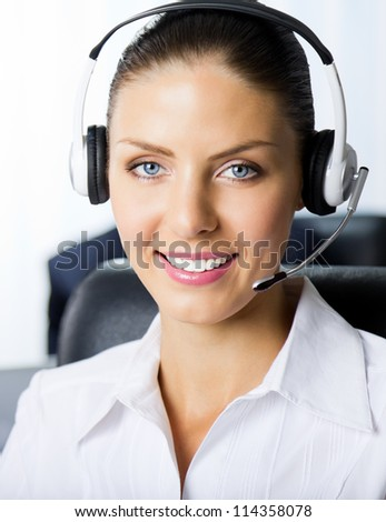 Portrait of female support phone operator at workplace - stock photo