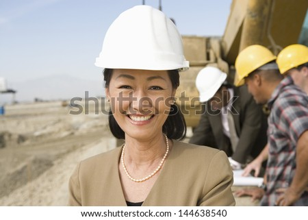 Portrait of female surveyor and construction workers on site - stock photo