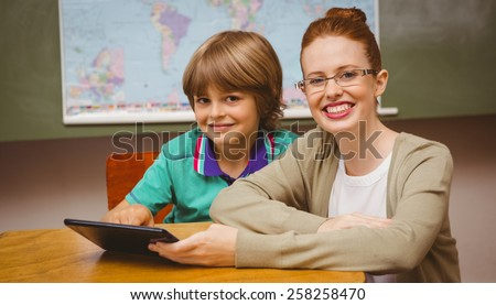 Portrait of female teacher and boy using digital tablet in the classroom - stock photo