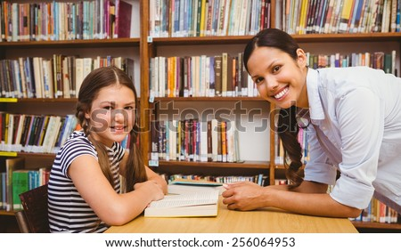 Portrait of female teacher and little girl in the library