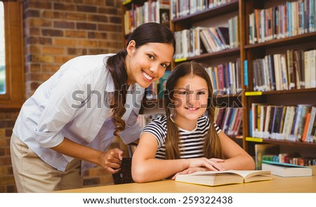 Portrait of female teacher and little girl in the library - stock photo