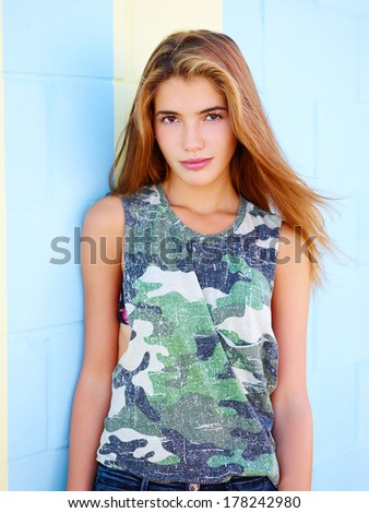 Portrait of female teenager on the street with colourful wall behind her - stock photo