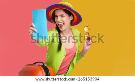 portrait of female tourist with travel suitcase and boarding pass - stock photo