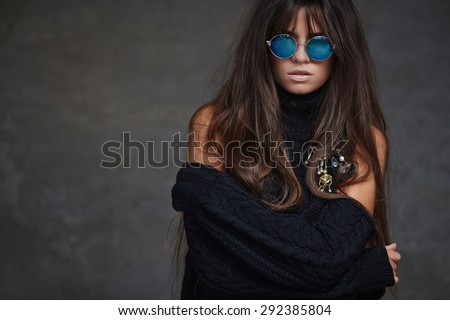Portrait of female with long brown hair in blue sunglasses and naked shoulders. Isolated on grey background. - stock photo