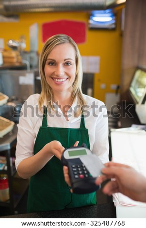 Portrait of female worker accepting payment from customer through credit card in bakery - stock photo