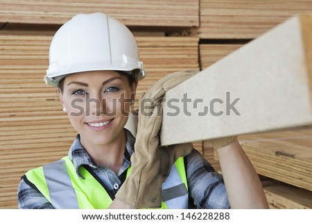 Portrait of female worker carrying wooden plank on shoulder - stock photo