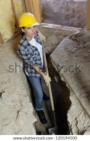 Portrait of female worker digging with shovel at construction site - stock photo