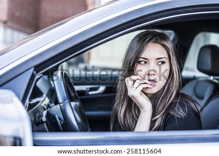 Portrait of female Young adult dreaming and looking far away girl sitting in luxury black car Slim cute asian scary woman listening music inside black leather chair auto hand Fingers caress big lips - stock photo