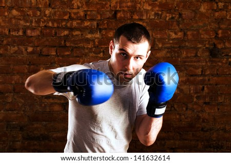 portrait of fighter in boxing pose against brick wall