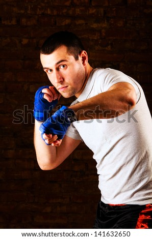 portrait of fighter in boxing pose against brick wall - stock photo