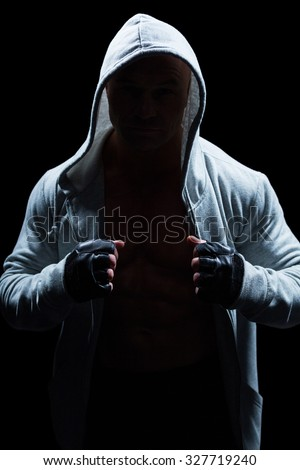 Portrait of fighter with hood and gloves against black background - stock photo