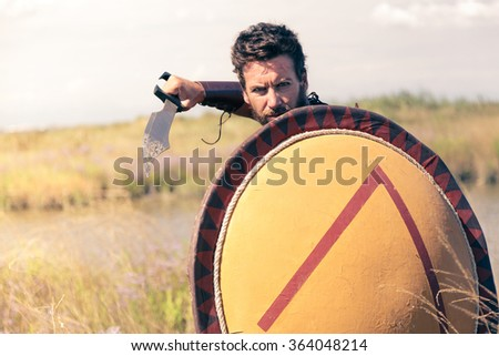 Portrait of fighting ancient warrior in armor with sword and shield. Spartan Soldier. Landscape background - stock photo