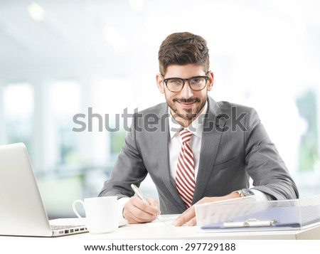 Portrait of financial advisor sitting at office in front of computer and working on business plan. Young businessman holding hands pen and making calculations.  - stock photo
