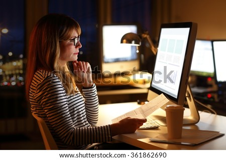 Portrait of financial assistant businesswoman sitting at office in front of computer and and holding in hand document while analyzing financial data late night. - stock photo