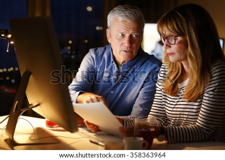 Portrait of financial assistant holding in her hand a document and consulting with director of finance while working late night at office in front of computer. - stock photo