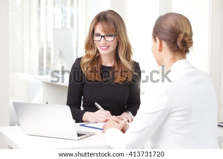 Portrait of financial consultant sitting with her client while discussing at office.  - stock photo