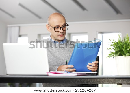Portrait of financial director sitting at office in front of computer and working on business report.