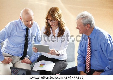 Portrait of financial manager holding digital tablet in her hands while consulting with sales men from annual report. Business team analyzing data at business seminar.