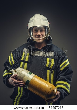 Portrait of firefighter in safety uniform holding yellow oxigen tank.