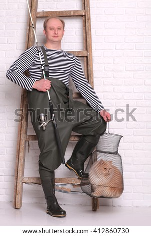 Portrait of fisherman in waders stands near the ladder, holding a fishing equipment - stock photo