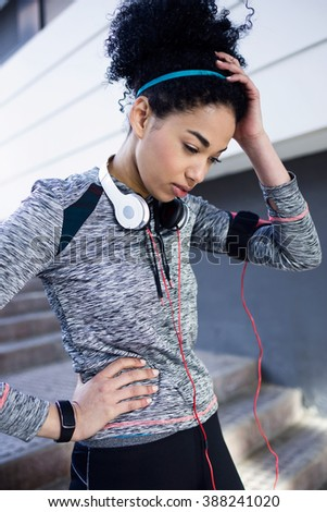 Portrait of fit and sporty young woman relaxing after work out in the park. - stock photo