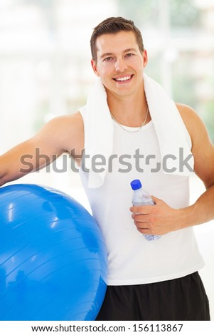 portrait of fit man holding water bottle and fitness ball