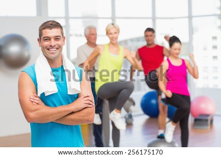 Portrait of fit man standing arms crossed with people exercising in background at gym - stock photo