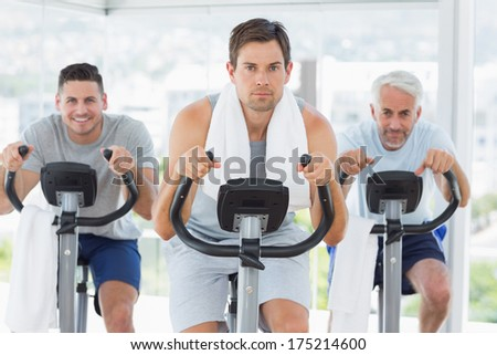 Portrait of fit man with friends on exercise bikes at gym - stock photo