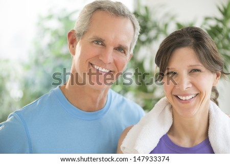 Portrait of fit mature couple smiling outdoors - stock photo