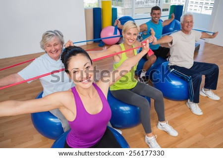 Portrait of fit people on fitness balls exercising with resistance bands in gym - stock photo