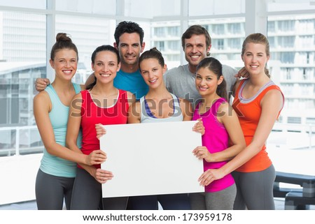 Portrait of fit smiling young people holding blank board in a bright exercise room - stock photo