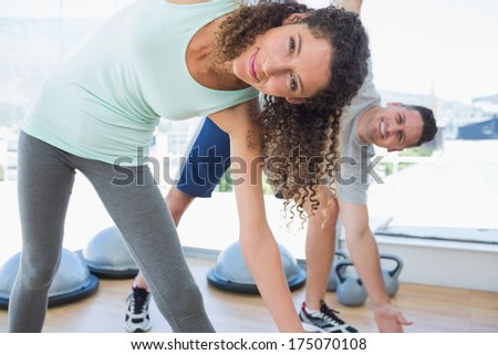 Portrait of fit woman with man doing stretching exercise at gym - stock photo