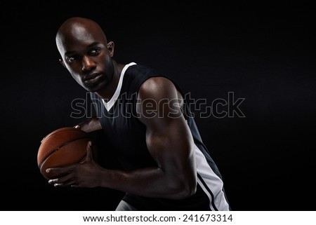 Portrait of fit young male athlete playing basketball looking at copyspace. African american basketball player against black background - stock photo