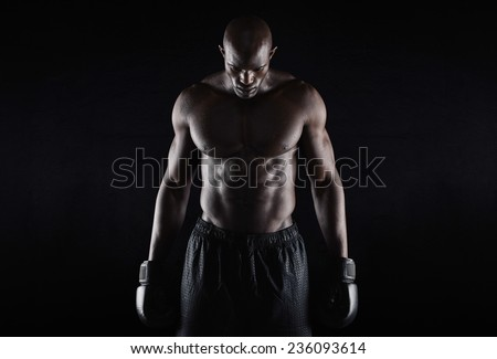 Portrait of fit young man wearing boxing gloves looking down on black background. Professional african boxer. - stock photo