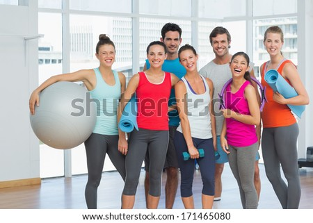 Portrait of fit young people smiling in a bright exercise room - stock photo