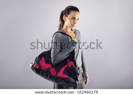 Portrait of fit young woman carrying gym bag looking away at copyspace over grey background. Beautiful caucasian female ready for gym exercise. - stock photo