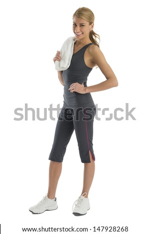 Portrait of fit young woman in sports clothing with towel standing against white background - stock photo