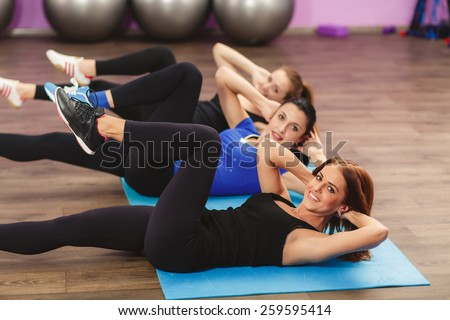 Portrait of fitness class and instructor doing stretching exercise on yoga mats. Group of people in a gym doing aerobics or warming up with gymnastics and stretching exercises - stock photo