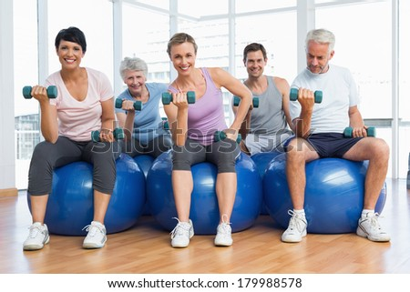 Portrait of fitness class with dumbbells sitting on exercise balls in a bright gym - stock photo