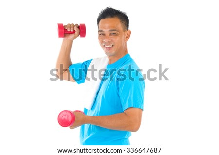Portrait of fitness man working out with free weights in studio