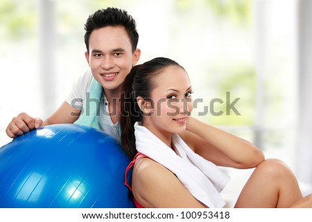 portrait of Fitness. Smiling young man and woman after workout in the gym - stock photo