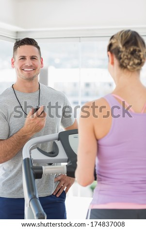 Portrait of fitness trainer holding stopwatch with woman exercising on treadmill - stock photo
