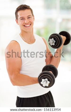 portrait of fitness young man at the gym doing exercises - stock photo