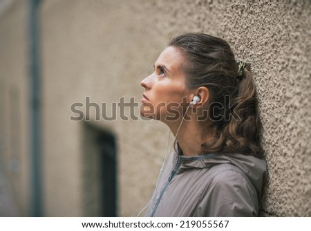 Portrait of fitness young woman listening music outdoors