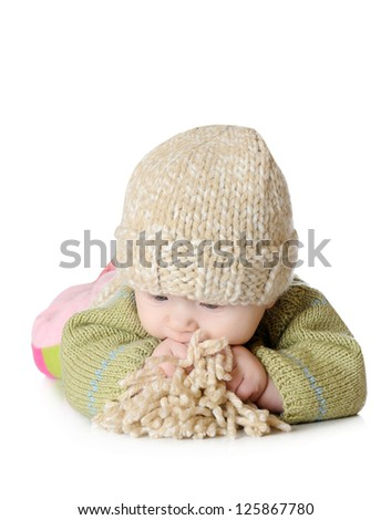 Portrait of five months old baby girl wearing knitted winter hat and eating pompon