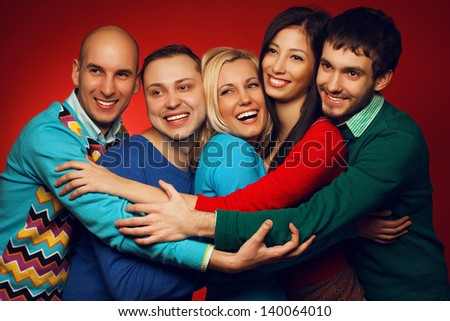 Portrait of five stylish close friends hugging and posing over red background. Guys having fun. Shiny smile and healthy white teeth. Hipster style. Studio shot - stock photo